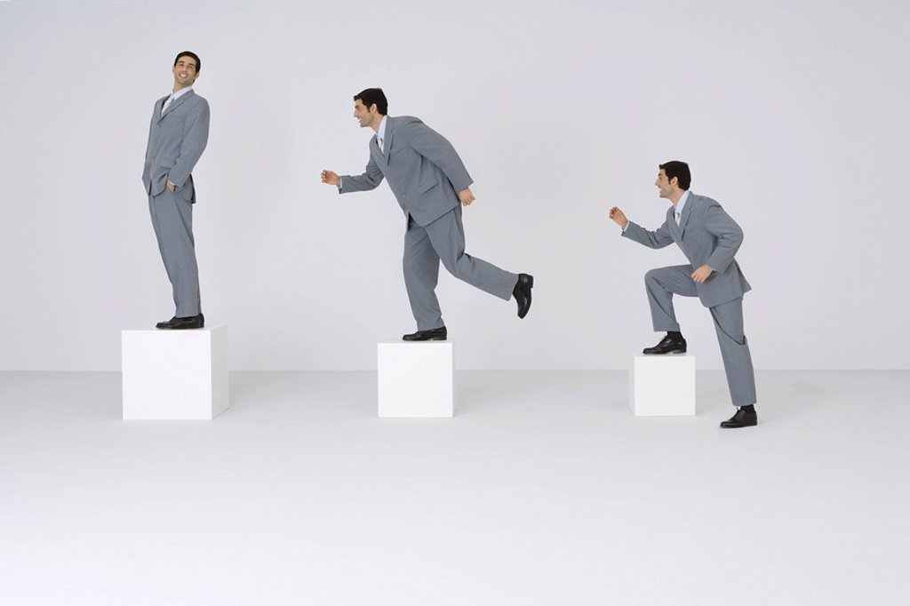Identical businessmen climbing gradually larger blocks : Stock Photo