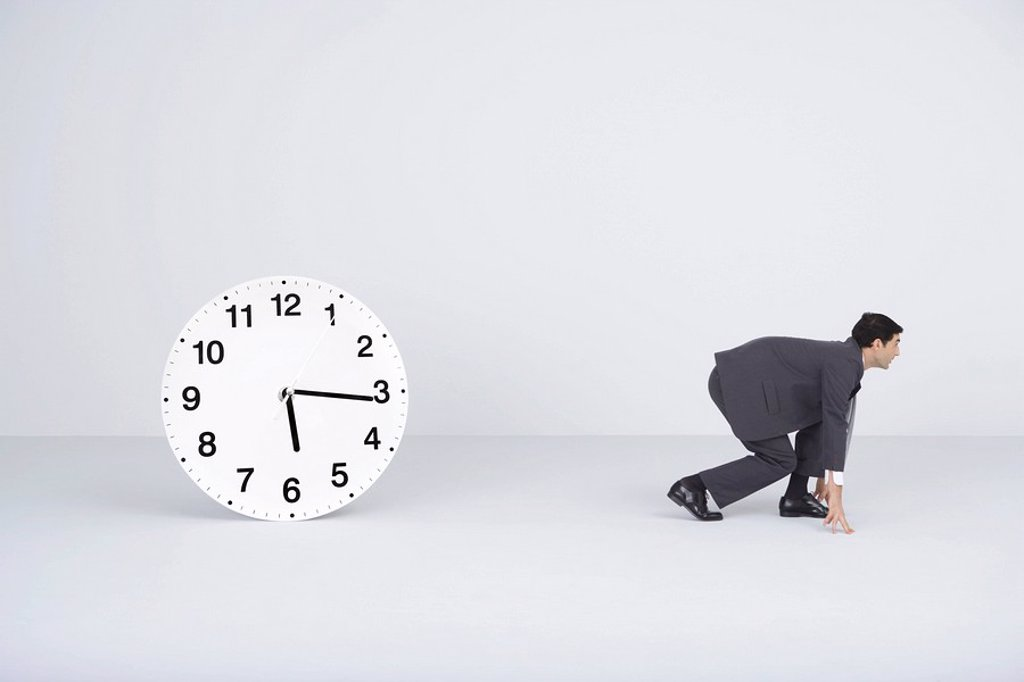 Businessman crouching, ready to run, next to clock : Stock Photo