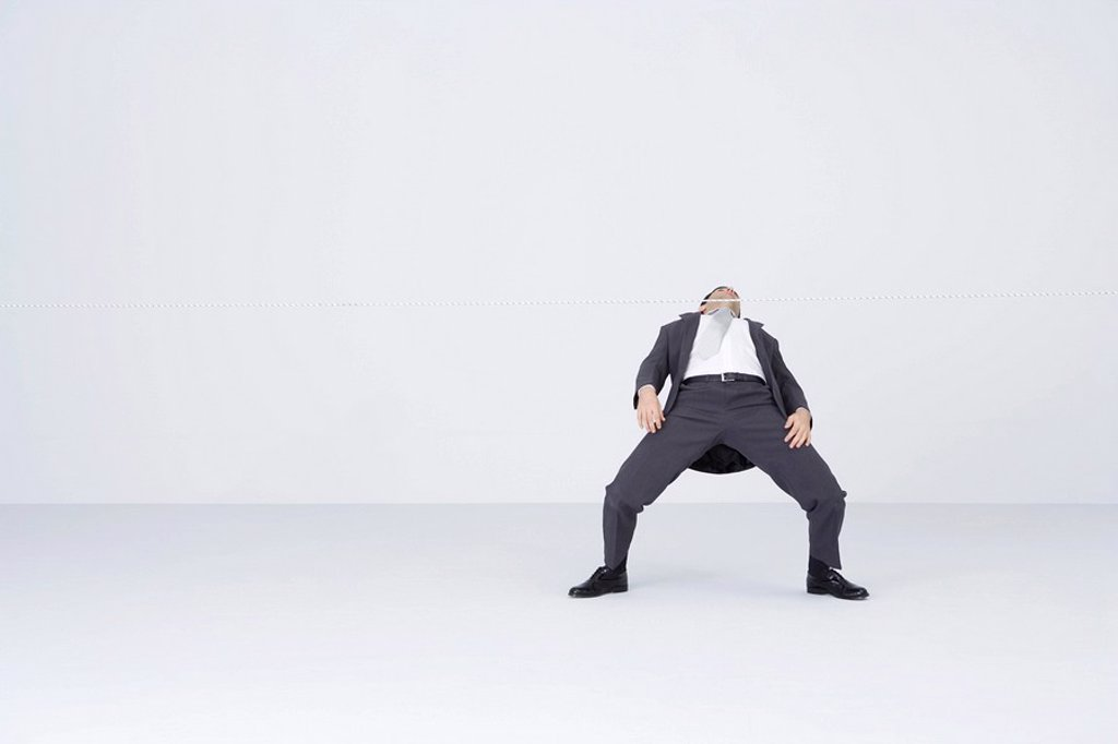 Businessman doing limbo, bending backwards to go under rope : Stock Photo
