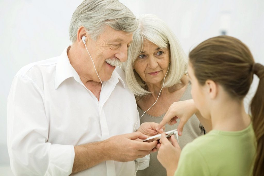 Young girl showing grandparents how to use MP3 player : Stock Photo