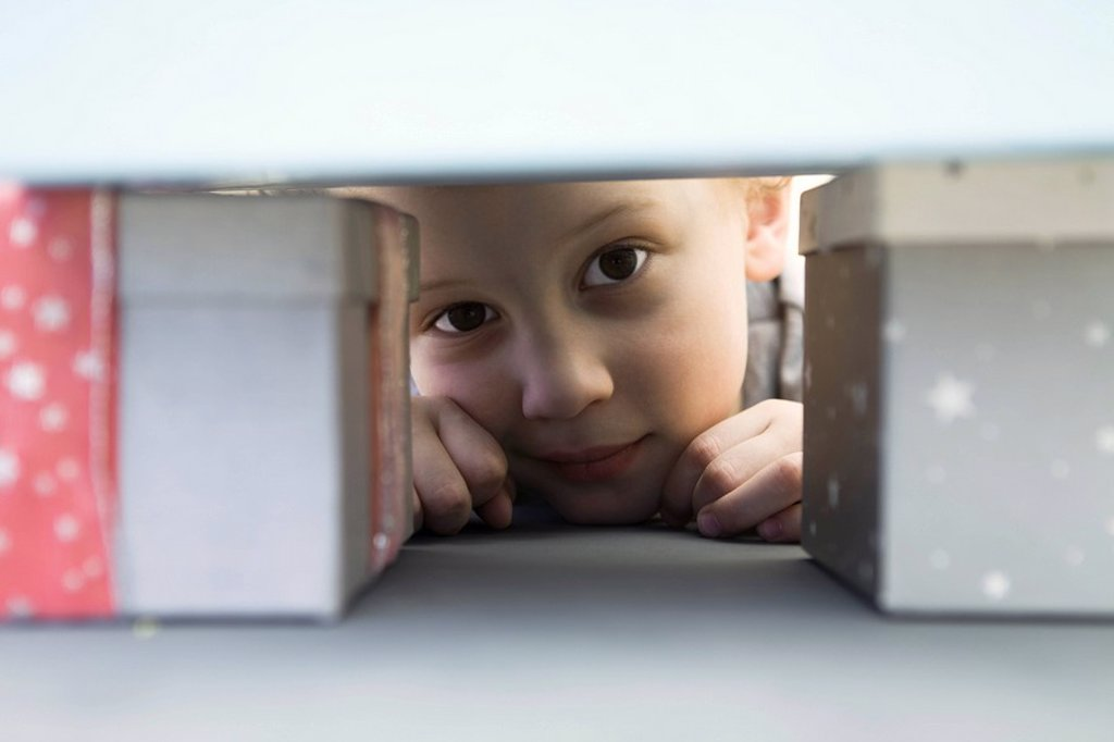 Little boy hiding behind pile of presents, peeking at camera : Stock Photo