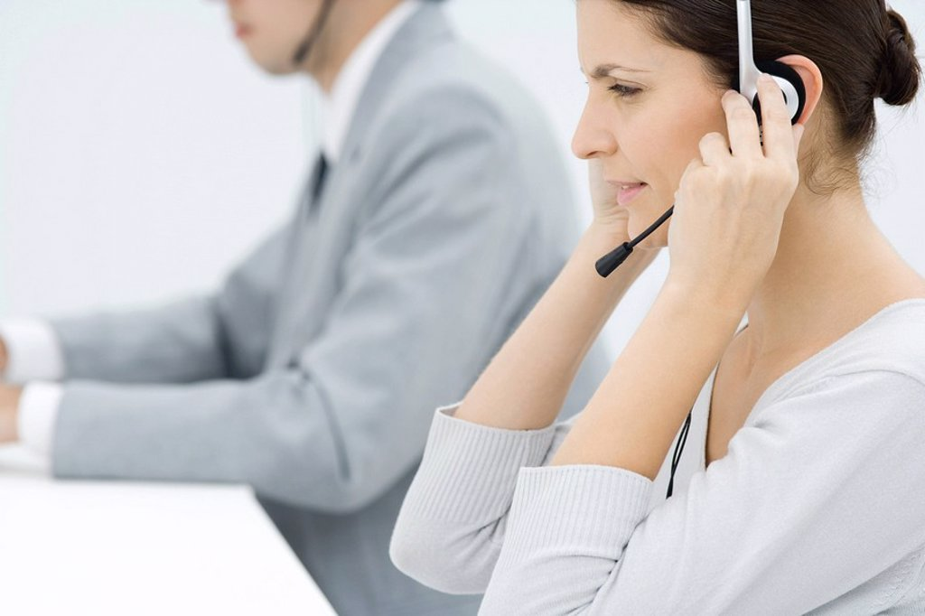 Stock Photo: 1569R-9039813 Professional woman adjusting headset, male colleague in background, side view