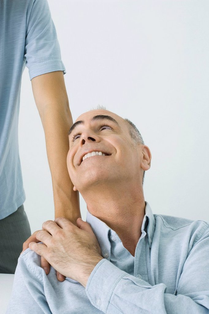 Mature man holding son´s hand on shoulder, smiling up over shoulder, cropped view : Stock Photo