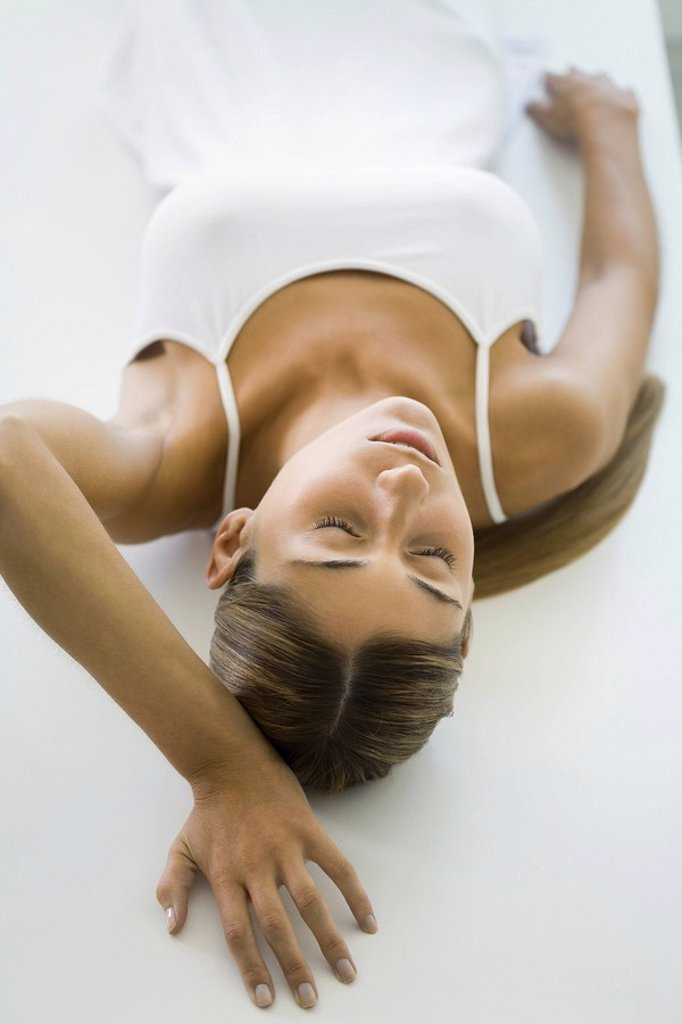 Stock Photo: 1569R-9039875 Woman lying on back, eyes closed, high angle view