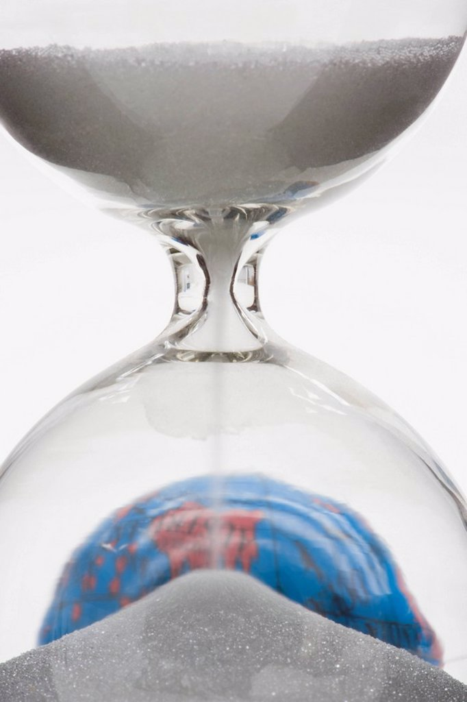 Hourglass, globe in background : Stock Photo