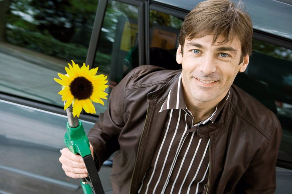 Man at gas station holding gas nozzle with sunflower emerging from end : Stock Photo