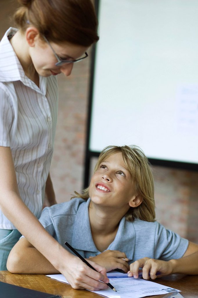 Student looking up at teacher smiling as they grade their classwork : Stock Photo