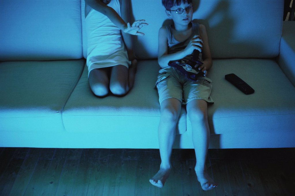 Stock Photo: 1569R-9040359 Boy playing video game, sister reaching for joystick