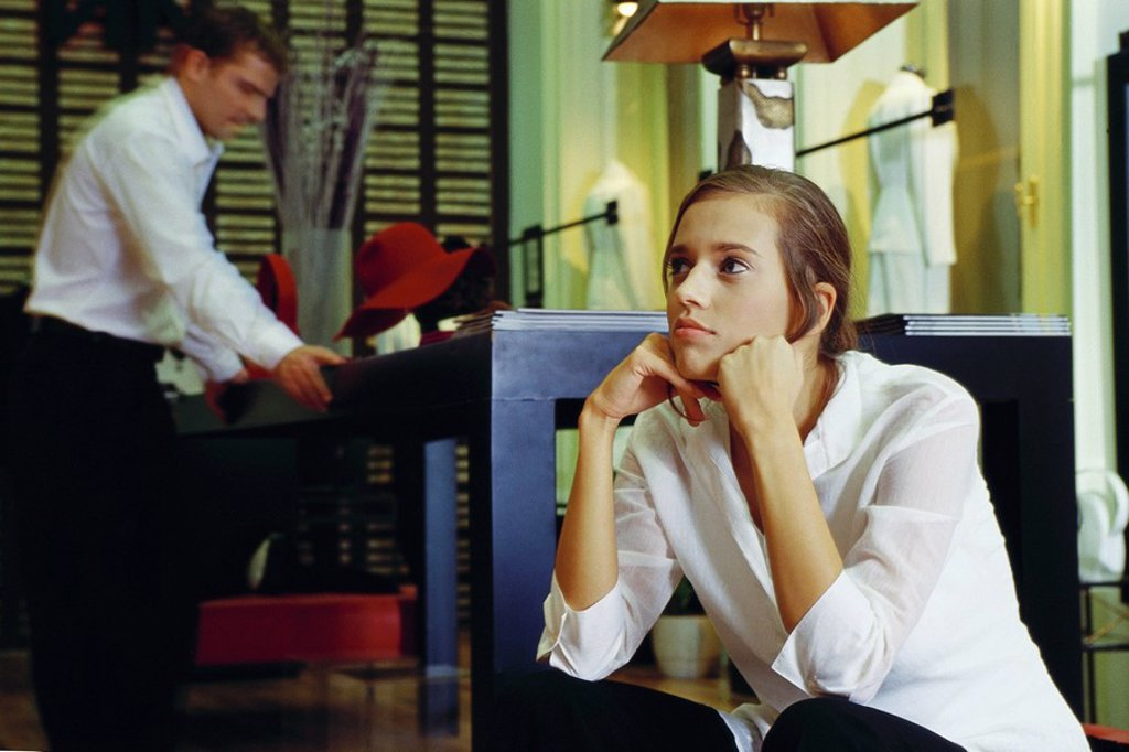Young woman sitting with hands under chin in clothing store, man looking at table in background : Stock Photo