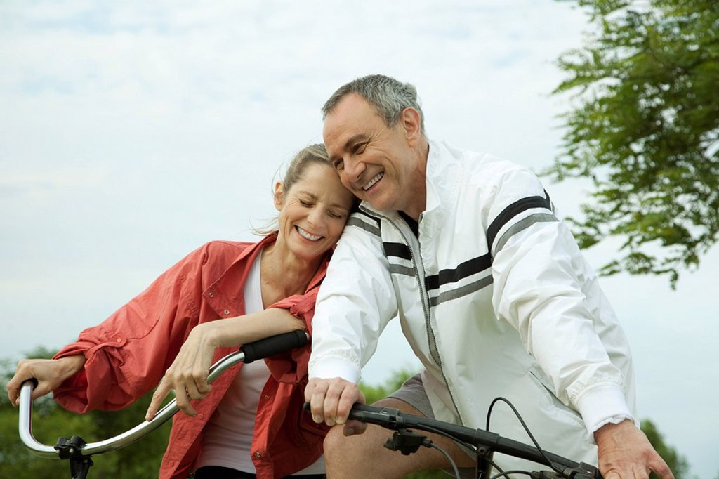 Mature couple riding bikes, leaning against each other : Stock Photo