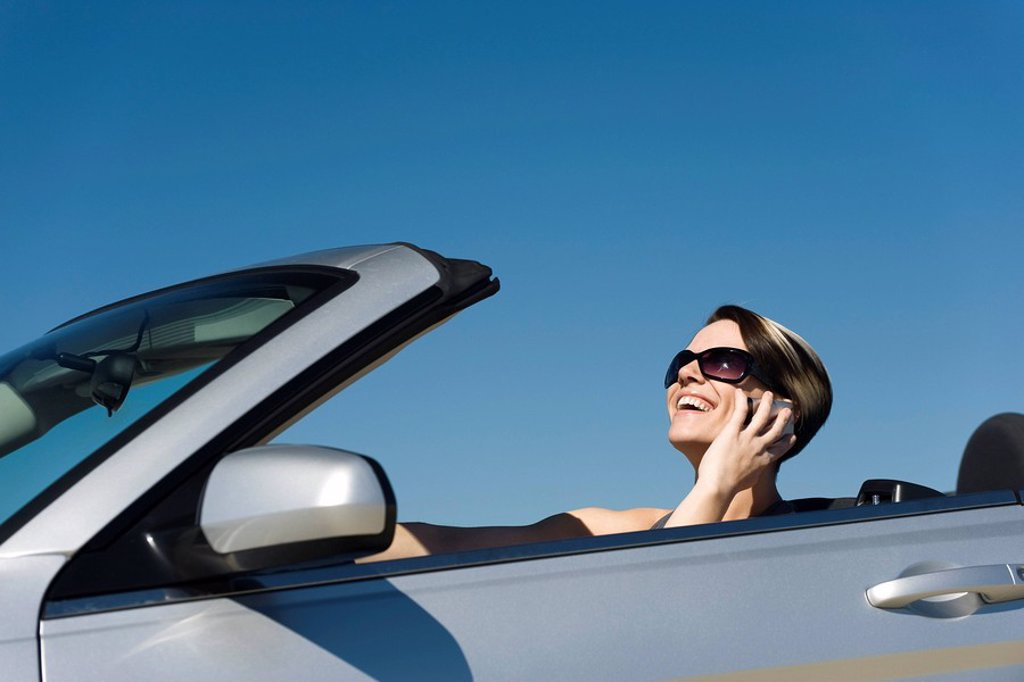 Woman talking on cell phone while driving convertible : Stock Photo