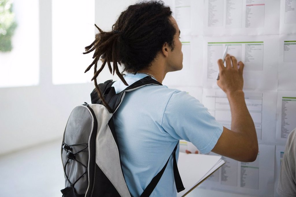 Stock Photo: 1569R-9040853 Male college student checking bulletin board