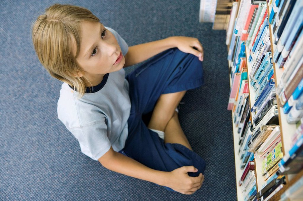 Stock Photo: 1569R-9040891 Boy sitting on floor looking up at rows of books lining bookcase