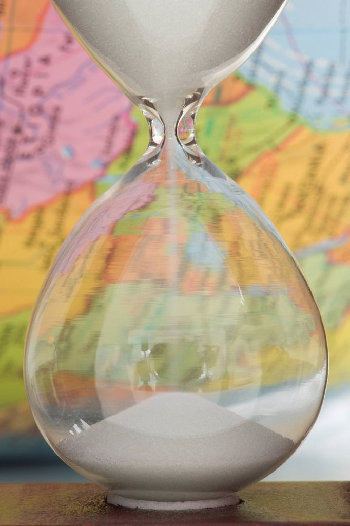 Hourglass, map in background : Stock Photo