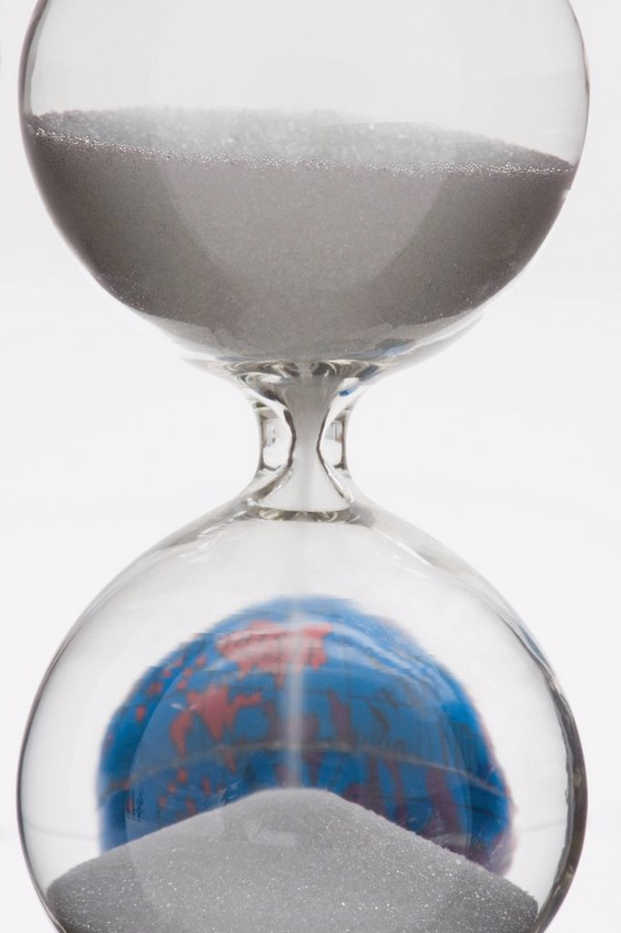 Stock Photo: 1569R-9040916 Hourglass, globe in background