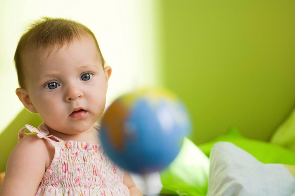 Infant girl contemplating toy globe : Stock Photo