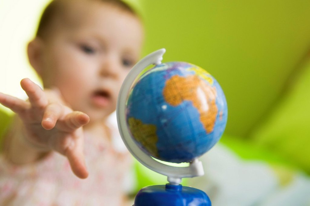 Stock Photo: 1569R-9041095 Infant girl reaching for toy globe