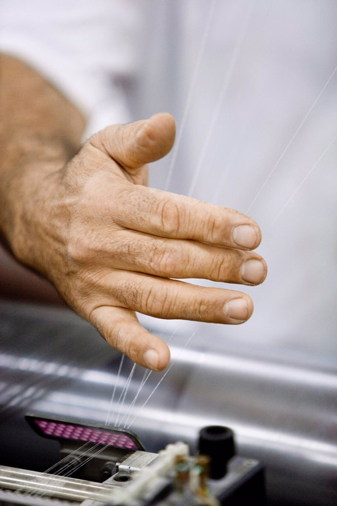 Machinist checking thread tension on loom in weaving mill : Stock Photo