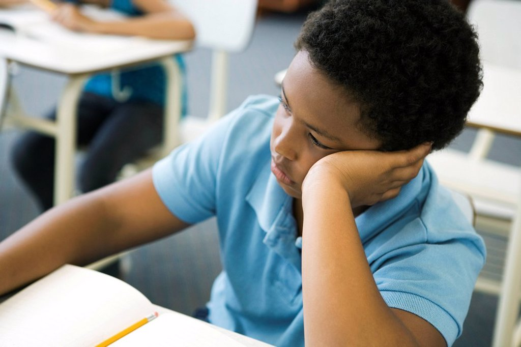 Male elementary school student bored in class : Stock Photo