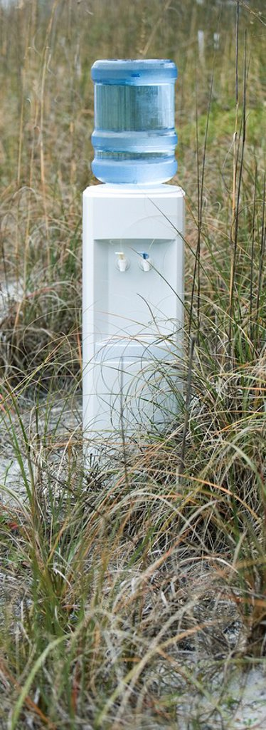 Water cooler in field of dry grass : Stock Photo