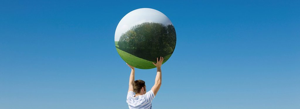 Holding aloft globe displaying image of forest : Stock Photo