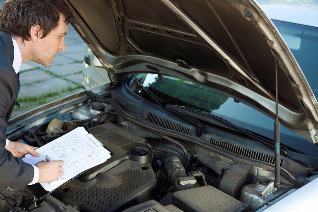 Stock Photo: 1569R-9042100 Inspecting car engine