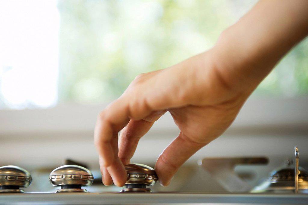 Hand adjusting stove knob : Stock Photo