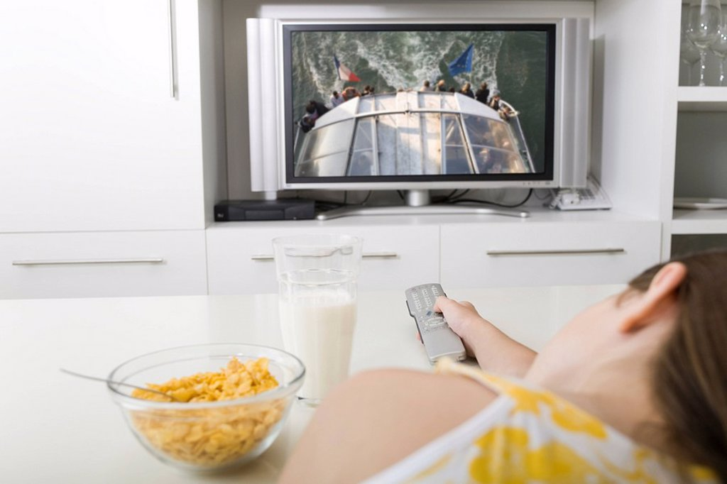 Watching television while having breakfast : Stock Photo