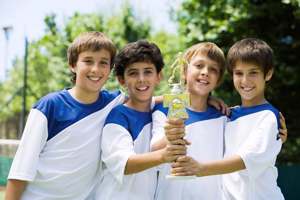 Young soccer teammates holding trophy together, portrait : Stock Photo