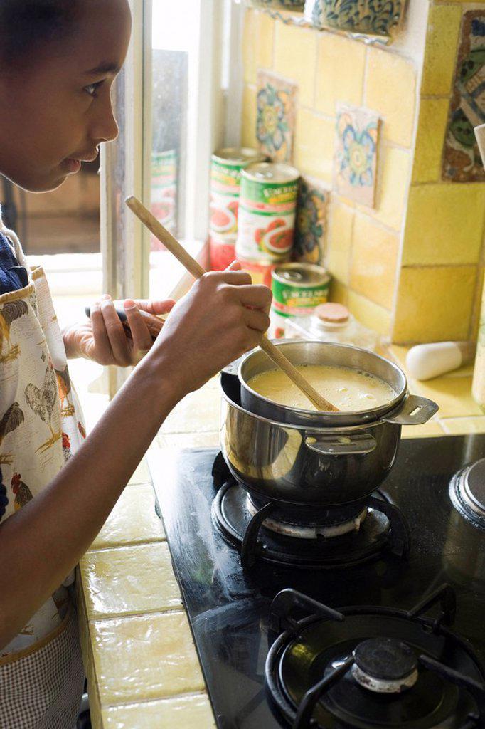 Stock Photo: 1569R-9042632 Girl stirring pot on stove