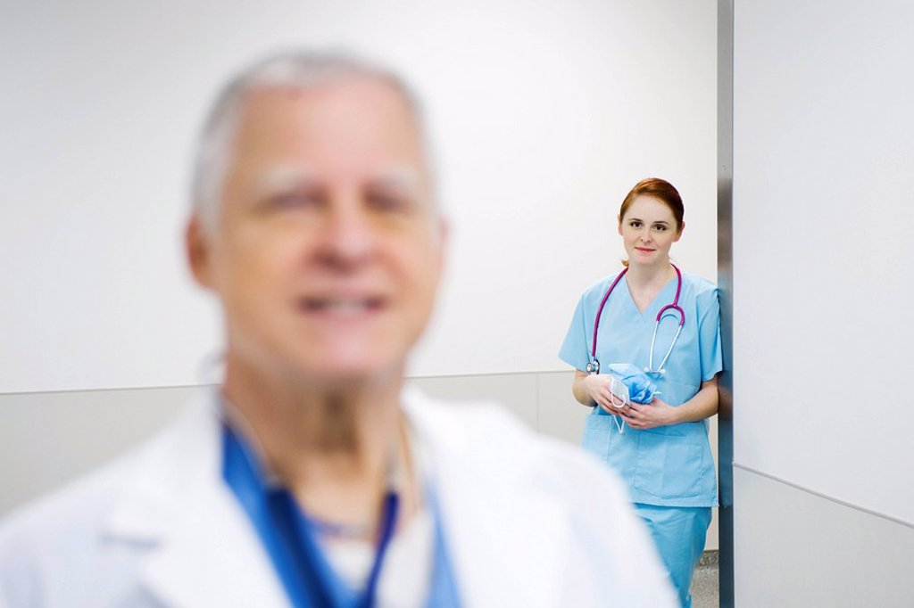 Stock Photo: 1569R-9042713 Nurse leaning against wall looking with admiration at doctor