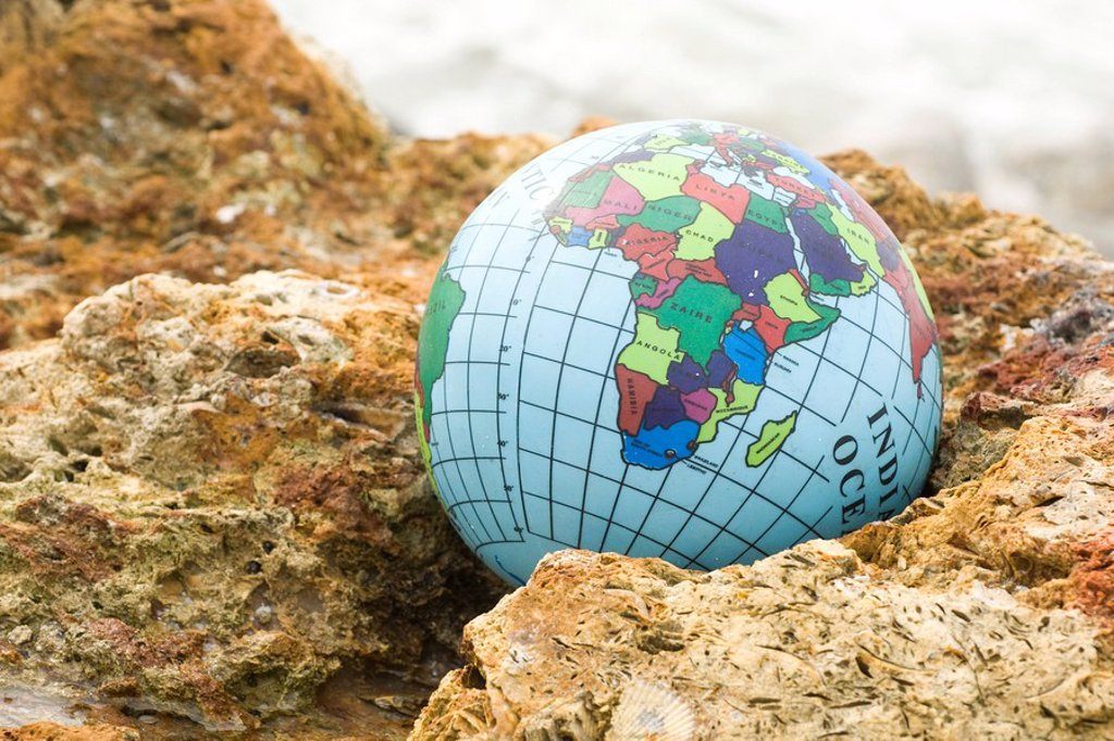 Globe nestled in rock : Stock Photo