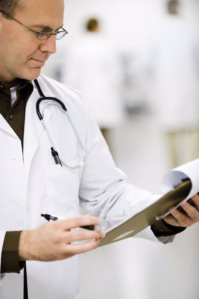 Stock Photo: 1569R-9042930 Doctor looking at medical chart