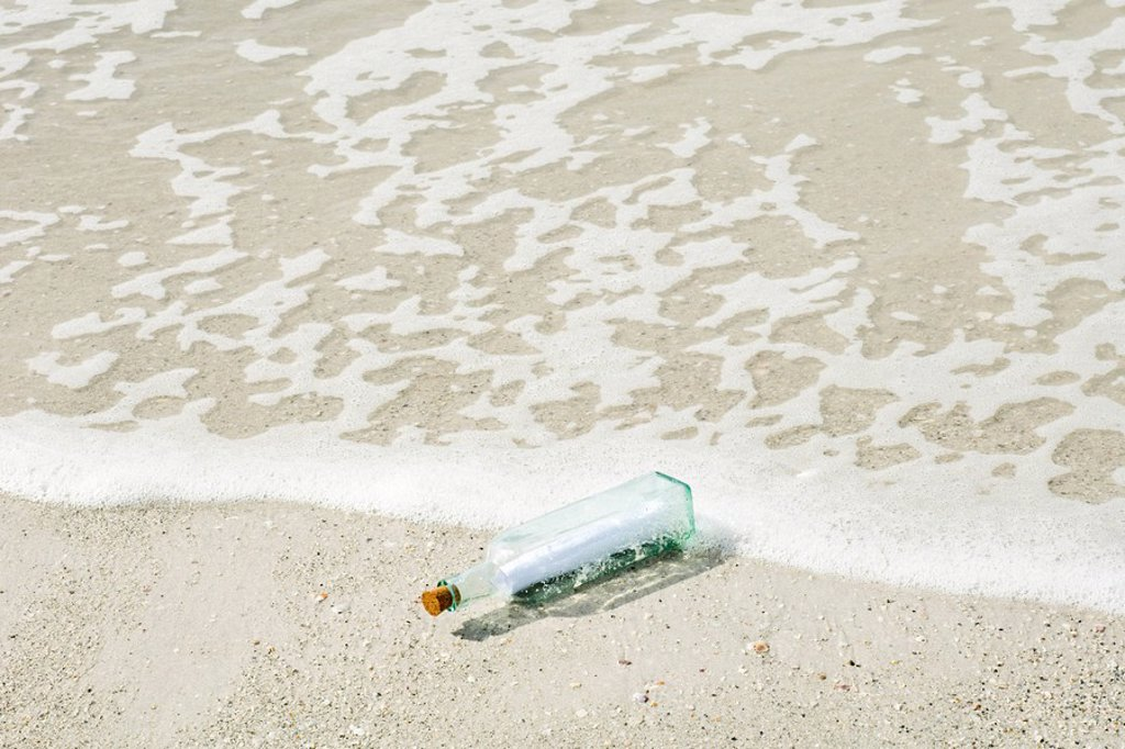 Message in a bottle washed up on shore : Stock Photo