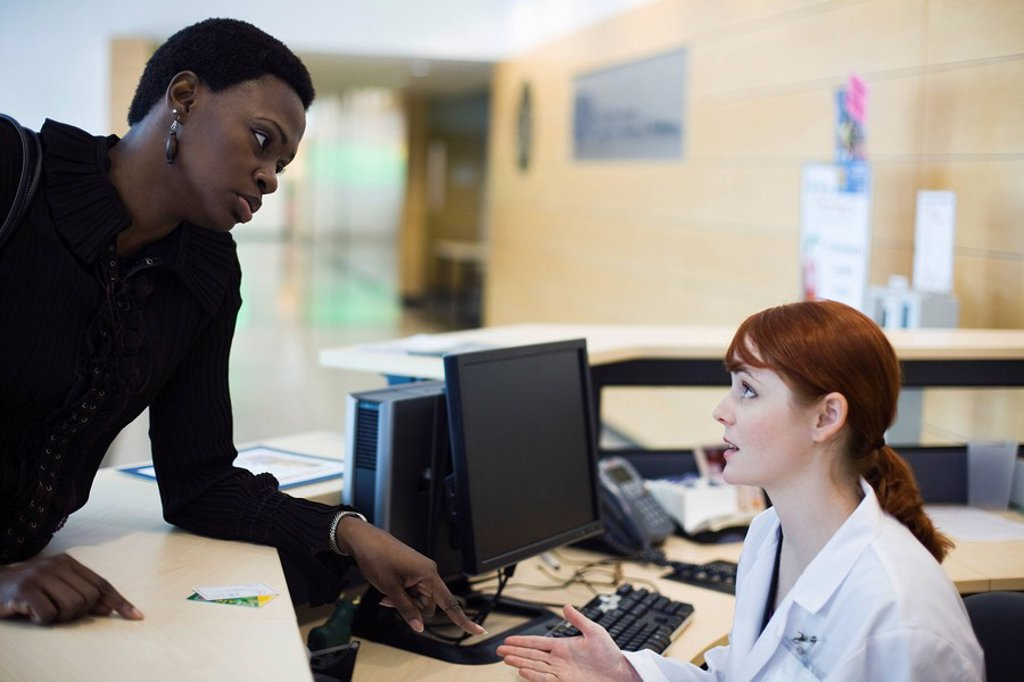 Stock Photo: 1569R-9043171 Female patient explaining problem to medical receptionist