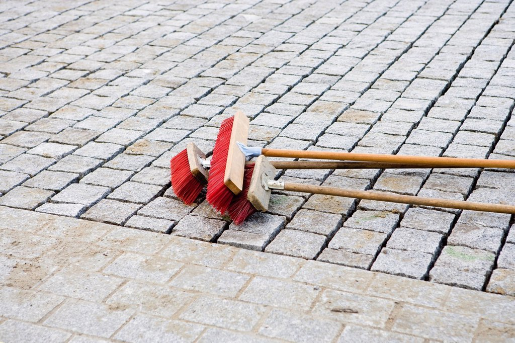 Brooms on cobblestone street : Stock Photo
