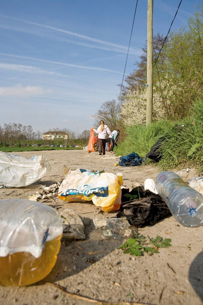 Trash dumped on dirt road, volunteers in background cleaning up : Stock Photo