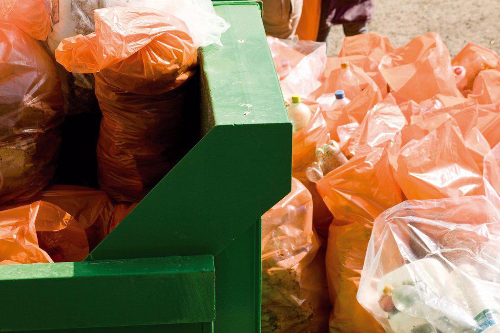 Garbage bags beside full dumpster : Stock Photo