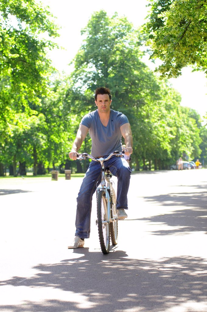 Stock Photo: 1569R-9043650 Young man riding bicycle