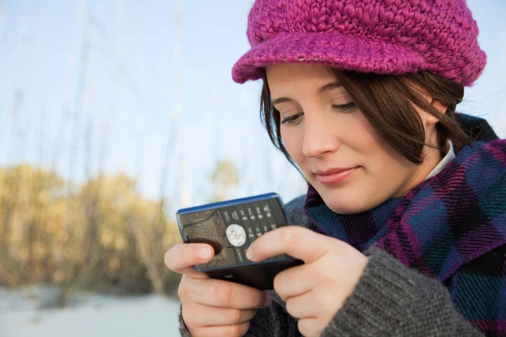 Teen girl text messaging at the beach : Stock Photo