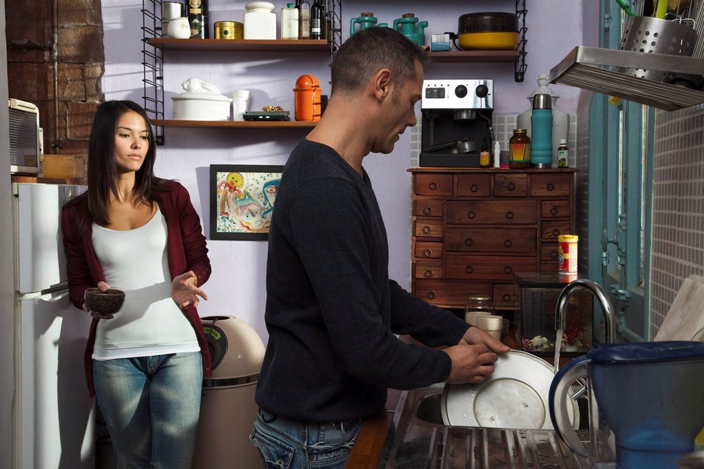 Stock Photo: 1569R-9044151 Couple in kitchen, husband doing dishes