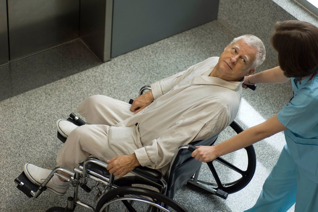 Nurse pushing senior patient in wheelchair : Stock Photo