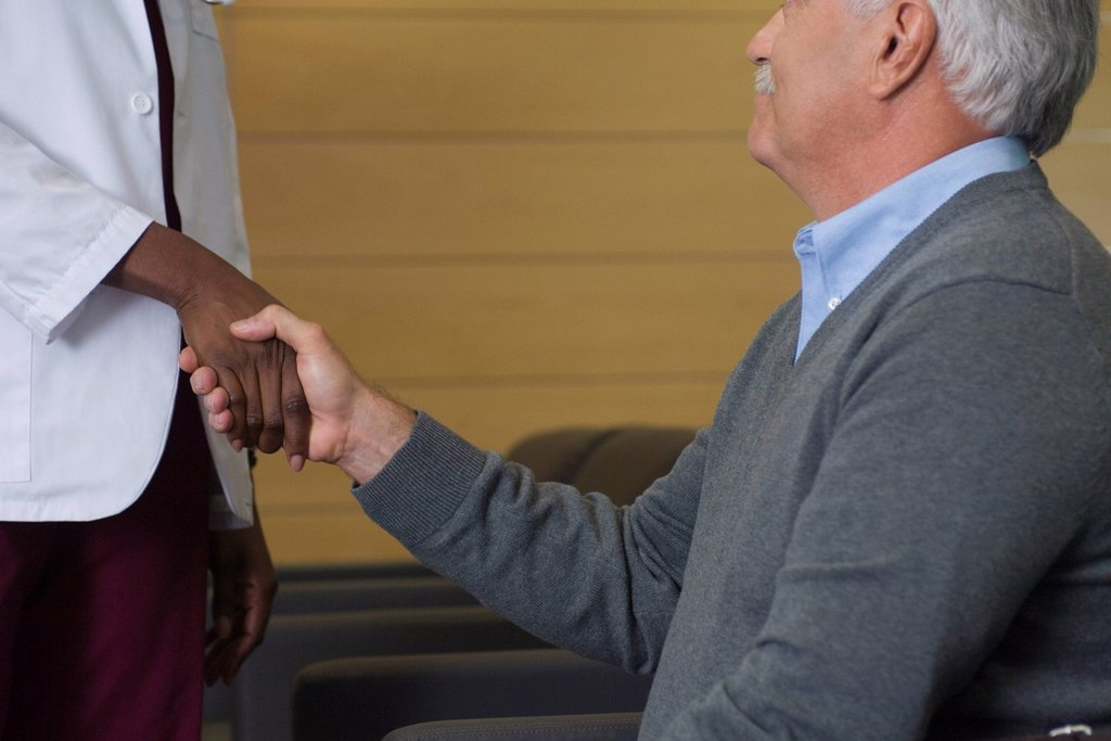 Stock Photo: 1569R-9044225 Man shaking hands with healthcare worker in waiting room