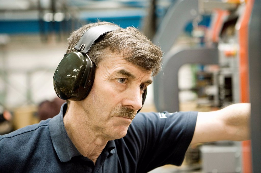 Factory worker wearing protective headphones : Stock Photo