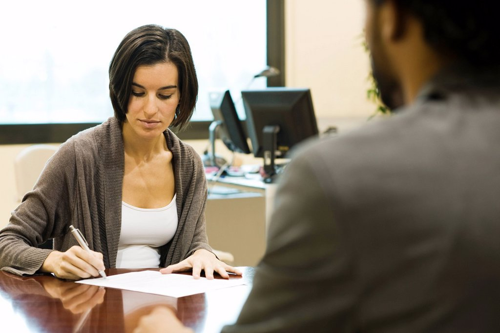 Woman signing document in office : Stock Photo