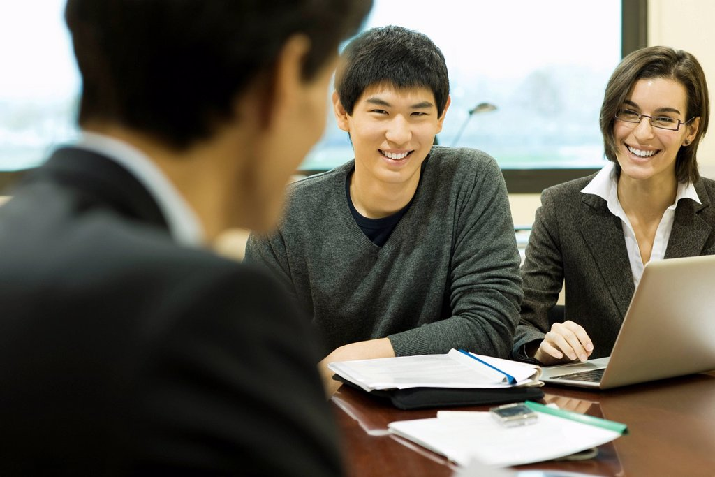 Stock Photo: 1569R-9044551 Executives in meeting, smiling at each other