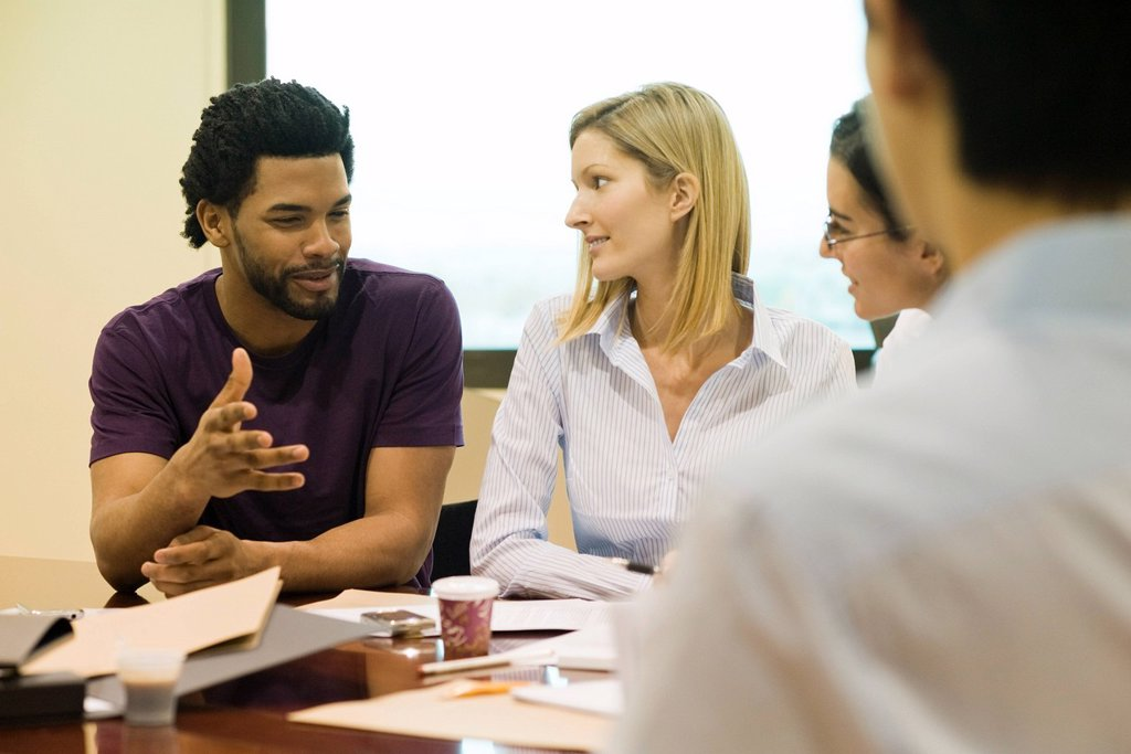Executives listening to colleague in meeting : Stock Photo