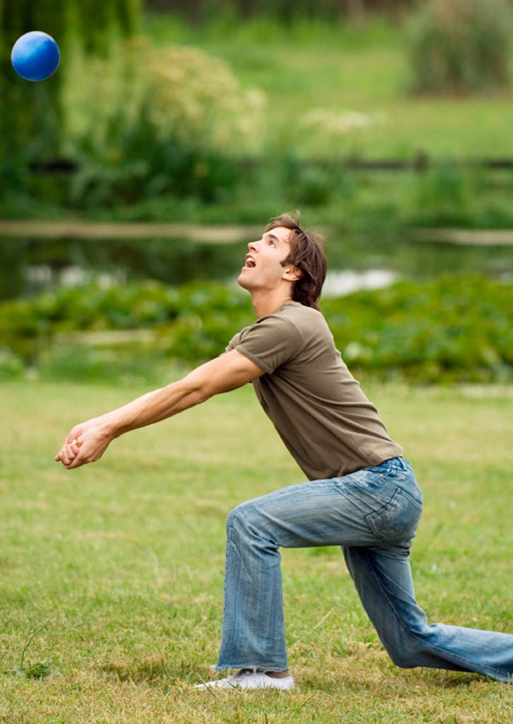 Man kneeling to hit volleyball : Stock Photo