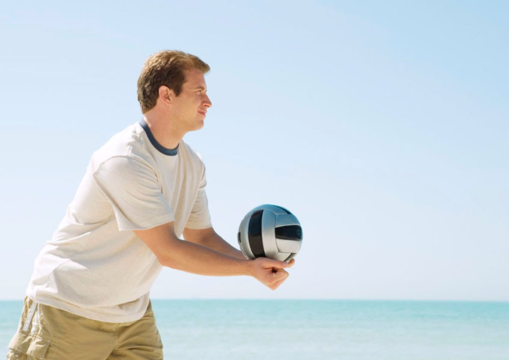 Stock Photo: 1569R-9044917 Man serving volleyball on beach