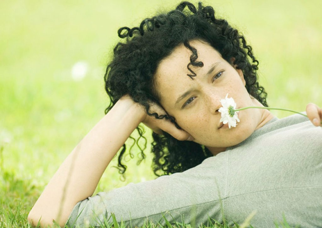 Stock Photo: 1569R-9044999 Woman lying on ground and holding daisy to nose